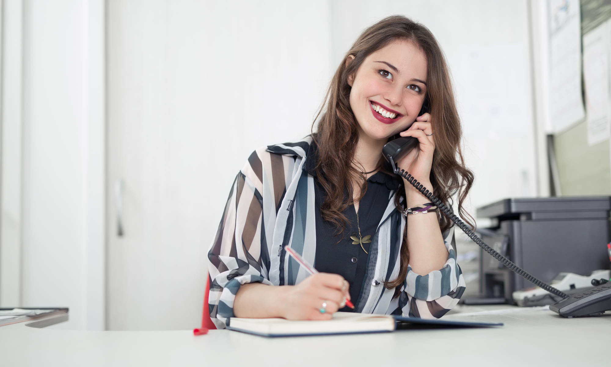 """Featured image for """"Contact Us"""" page of Piano Lessons Knoxville dotcom depicting pretty woman in office setting smiling while talking on the office phone and writing in a book."""