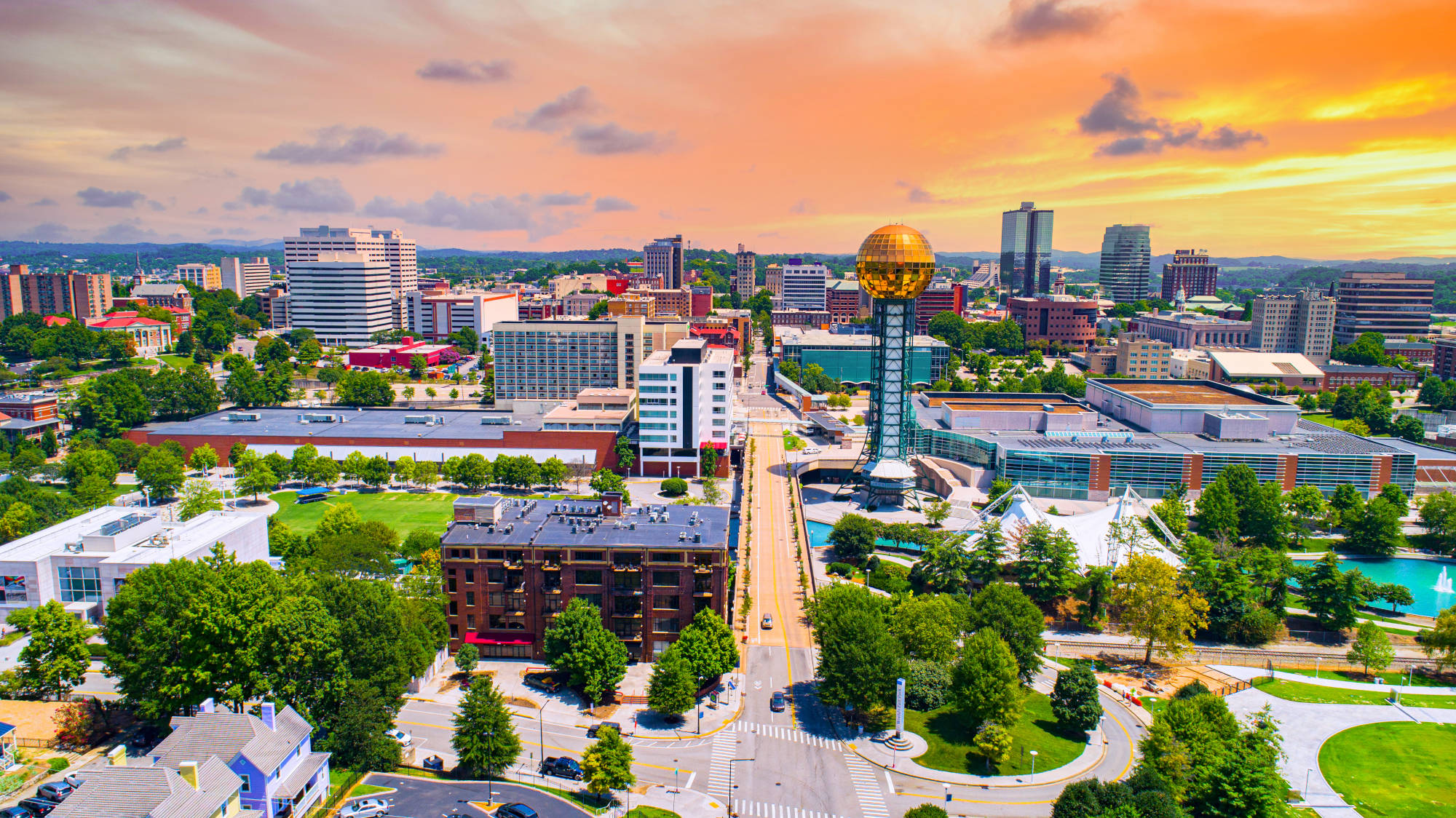 Image of downtown Knoxville with enhanced colors - lush green grass, shiny buildings, and beautiful sunset sky with orange and purple hues.
