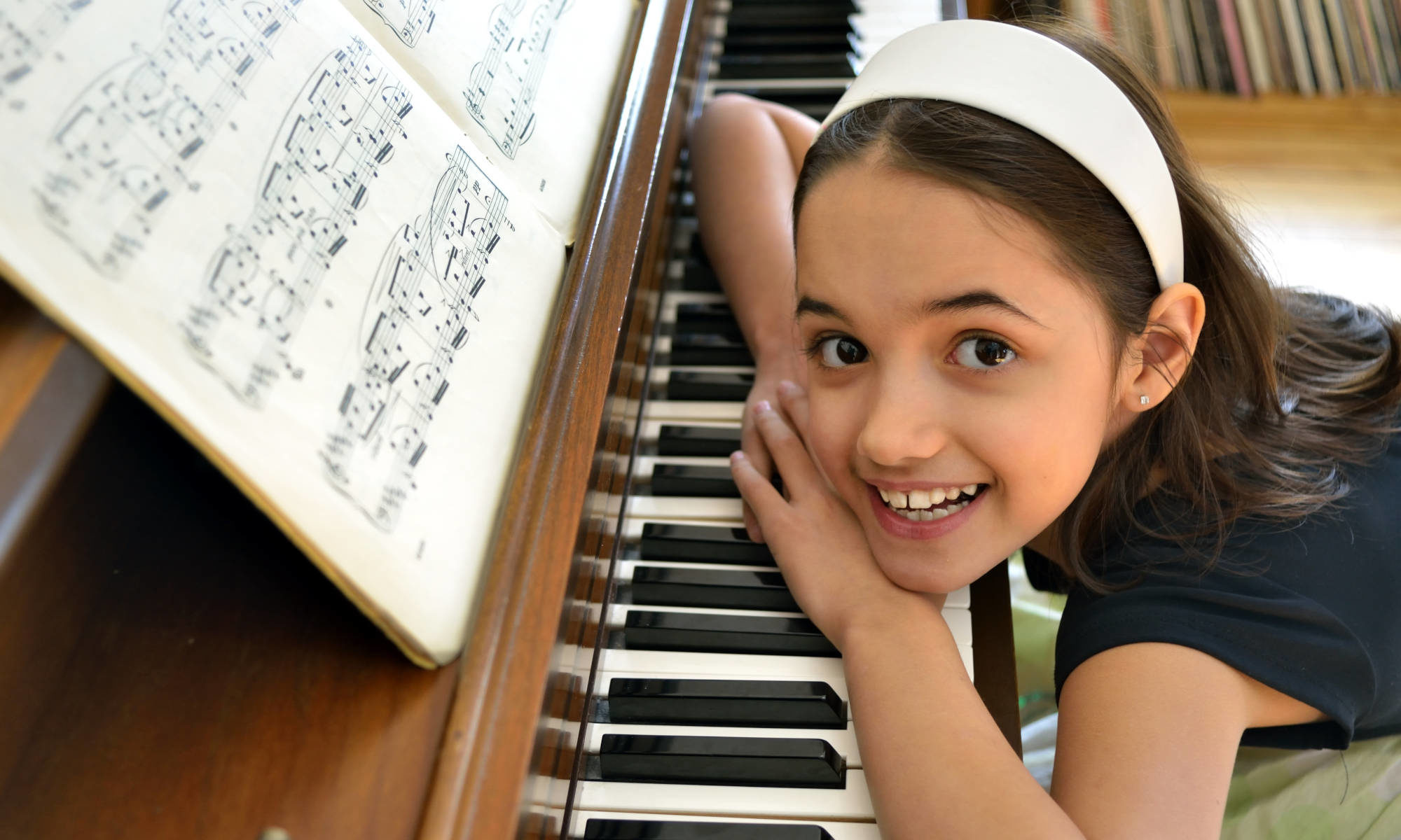 """Featured image for """"Piano Lessons"""" page depicting young girl with big smile sitting at piano and looking up at camera."""