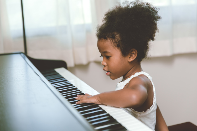 Featured image for Piano Lessons for Children section of Piano Lessons Knoxville dotcom depicting a pre-Kindergarten girl touching the keys of a piano.