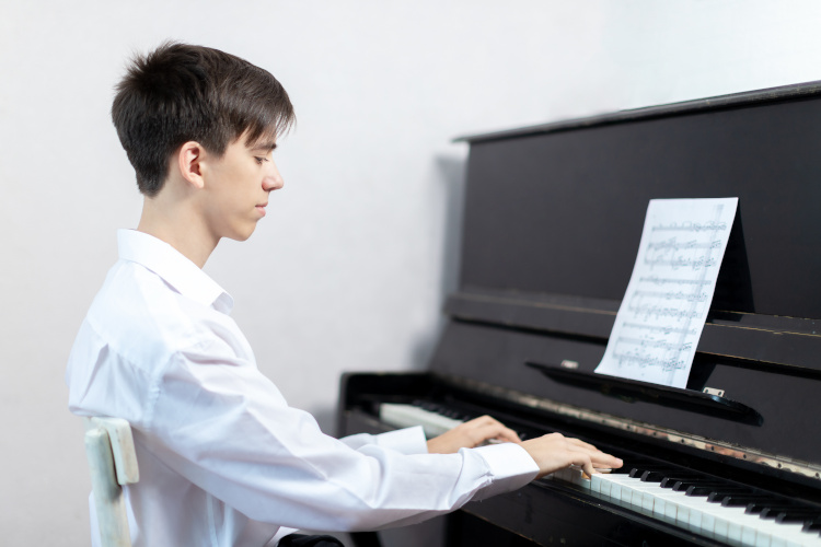 Featured image for Piano Lessons for Teens section of Piano Lessons Knoxville dotcom depicting teen boy in white shirt playing a black upright piano.